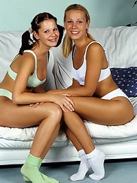 Two teen girls kiss and fondle on the couch : They kissed, caressed, and fondled each other while they smiled pretty for