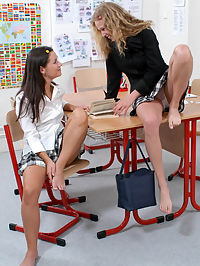 Two schoolgirls kissing in the classroom
