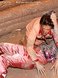 Naked girls wrestling fighting and covered in mud in a club