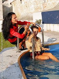 Three hot fully clothed lesbian babes playing in the pool