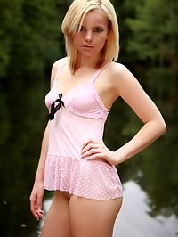 Beautiful teenager shows her naked body outside near water