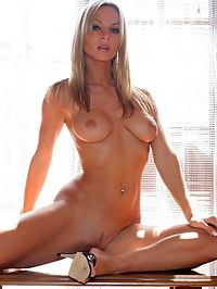 Naked and big breasted blonde spreading her long sexy legs