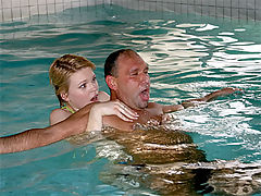 Blonde teenage swimming teacher helping a drowned senior