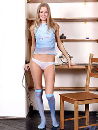 Blonde petite teen posing on the chair after taking off her clothes