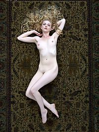 Lovely blonde nymph poses nude on Persian rug