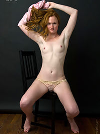 Redheaded cutie lets her hair down and strips.
