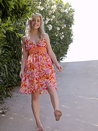 Sweet teen Kara in the garden wearing her classy, floral dress and flashing her goodies in public