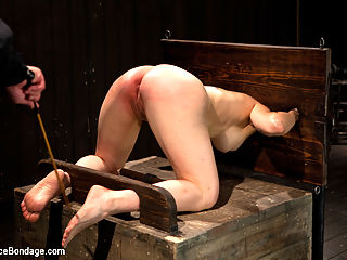 Big Breasts, Big Mouth, Big Orgasms : Busty Annika learns the ways of rigid bondage.She is stuck in doggy by wooden stocks. Her knees hard pressed and her weight on her wrists and neck. while the position wears her down the hard caning ramps her up only to be ass fucked into a strangulating orgasm .Bent back and metal strapped down, the unsuspecting soon to be pain slut is arched and spread. Her neck is chained and pulled back restraining her from seeing whats about to happen to her. The zipper is methodically placed onto her sensitive skin and viciously ripped off to create an explosive orgasms.With her mouth filled with an over sized bit gag, Busty Annika is lifted off the ground by the sybian. Her ankles are locked tight pulling her pussy onto the vibrating machine and the nipple tuggers accentuate her big breasts. She is immobile and relentlessly vibed into a pouring sweat.