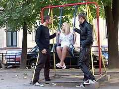 2 guys pick up a little girl at the playground