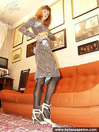 Pantyhose redhead girl poses on a sofa