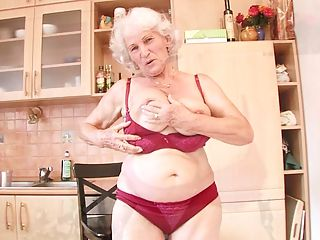 Grey haired grandma fucks her hairy twat with a toy after making cookies