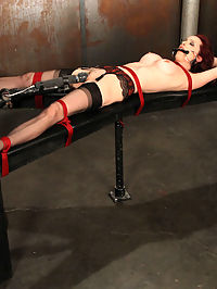 Emily roped to the bench in bondage orgasms. : I really cant decide which is more arousing, Emilys mouthwatering body, or seeing her struggle, bound tightly in red rope...Being the selfish bastards that we are...lets have both and then some shall we? Weve removed her top revealing those amazing tits, which of course weve tightly entwined...She puts up a struggle for us that gets our hearts pounding...We then restrain her to bench and bit gag this lovely babe...Her whimpers are fierce, almost at times overpowering the purr of the vibe pulsing against her cunt...It doesnt take long for Emily to give in to a white-hot, mind bending orgasm...We wish it couldve lasted forever though...