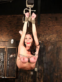 Busty Little Angel whipped enemas! : I made good plans...in the first scene I rig her for a single-ankle suspension...I blindfold, then Dom her as I rig her...I take her up, shove a dildo in her pussy and leave her to hang...She looked so fine hanging in there air...I decided to keep her there...we strip her of her clothes and boots, then I rig a two point, back bending, suspension...ankles and wrists...she hangs limp and bent as I cane her tummy, ass and legs...I give her good strokes...she should thank me for the endorphins...she needs a break so I bring her down...I take it to her feet with bands...then the ass hole gets stuffed...she struggles well as I try to vibrate her pussy...I pull her into the air again and allow her some well earned pleasure...I tie her spread on top of a palette, then I prop her up...she begs for the single tail...or not...I use it anyway...Do remember that Angel has a safe word...she plays the role deeply...but she has a safe word and uses it, and when she uses it, I stop...but she tries to manipulate me with begging and such...pay it no heed...this is a professional BDSM model and she knows she can end it all whenever she likes...the interaction is deeper than apearances with anyone who truly enjoys the role...and we took plenty of oportunities to check in with her...its a must with anyone who slips into endorphin fueled sub-space...