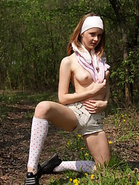 Pretty teen chick starts stripping in the forest in order to let you see her sexy body.