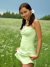 Marvelous nude babe with two pretty ponytails has a walk in the field of chamomiles and fondles her tender skin with them.