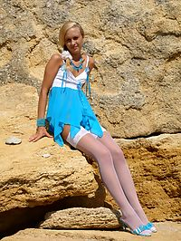 Savory blonde with long legs in white stockings stripping her blue dress and panties