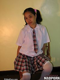 Asian in school girl uniform plays with her pussy through her white panties.