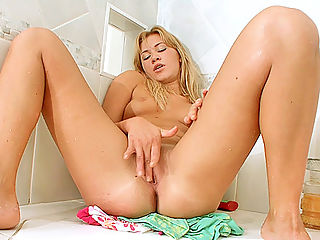 Desirable tan blonde finishes off her shower with a finger fuck