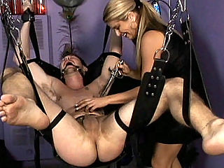 Mistress Nicolletes BDSM Ball Torture : Mistress Nicolette loves to collect bdsm toys and here, shes trying them all out on her new slave. She makes sure that he is bound tight and hanging so she could access his balls and cock. She then starts drippping hot candle wax on his hard balls.