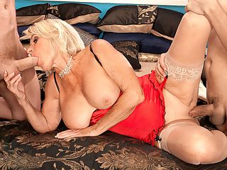Happy New Year! Georgette Is Fucking Two Guys! : Earlier in the year, we asked, Is Georgette Parks a slut or a classy lady? When this scene opens, 65-year-old Georgette looks very sexy but classy. Shes wearing red lingerie and stockings. And even when shes talking about getting fucked by two guys on camera for the first time, she still has that air of class.brbr br But then the camera pans down. Hey, Georgette isnt wearing any panties! Her shaved pussy is right there for all the world to see! And then we remember the answer to our question Georgette is a classy slut.brbr br The two guys show up, one on each side of her. I want you to fuck me, Slut Georgette says. I want to get fucked so bad. And I want to suck both of you.brbr br Georgette kneels between them and sucks one while jacking the other. Then she lays back and takes turns sucking one guy while the other fingers her pussy. When the fucking starts, there isnt a moment when Georgettes mouth and pussy arent simultaneously stuffed. Okay, there are a few moments when theyre changing positions.brbr br Question How much cum can Georgette coax out of two cocks at the same time? Youll have to watch the video to find out.brbr br Meanwhile, Happy New Year from Georgette and all of us at 60PLUSMILFS.COM. We hope your New Years Eve is as wild as Georgettes is going to be!