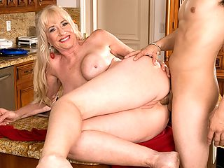 Delivery In The Rear : For her first on-camera fuck anywhere, 59-year-old Summeran Winters reenacts one of our favorite scenarios MILF seduces the delivery boy. Now, if youve ever been a delivery boy, you know this kind of thing happens all the time. Real-life MILFs really do seduce the delivery boy, whether its the pizza guy or the supermarket guy.brbr The thing is, though, usually, the delivery boy is on the receiving end of the best blow job of his life. In rare instances, he gets some pussy to fuck. But how often does he get to fuck the MILF in the ass? Almost never, which is what makes this scene so special. That and the fact that he gets to fuck Summeran in the ass on the kitchen table.brbr In my personal life, I love anal sex, so why wouldnt I want to have anal sex my first time in front of the camera, Summeran said. Some people make a big deal out of anal sex, but to me, whats the difference between me having a penis in my pussy or a penis in my ass?brbr By our estimate, a few inches, at most.