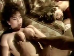 Orgy for four : A naked guy is on a couch. He is fucking a blonde girl who is sitting on his lap. Next to them another woman is laying on her back. She is getting fucked by a second guy. The other couple gets down on the floor where the first girl is fucked from behind.