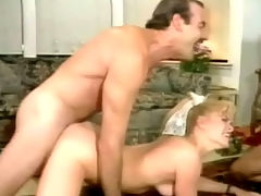 Blonde in a threesome : A blonde girl is sucking the dick of a guy who laying down on a couch. At the same time a second guy is fucking her hard from behind. The three of them move to the floor and the guys trade places, fucking the girl in her pussy and her mouth.