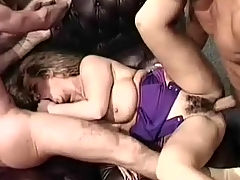 Busty girl in a threesome : A topless girl is standing in between two guys who play with her enormous boobs. A little later she is laying on the floor where one of the guys fucks her in between her tits while the other one licks her pussy.