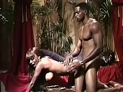 Jungle fuck : A black girl is fondling her naked breast while a black guy is watching her. She gets down on her knees to suck his dick. Then she goes on all fors so the guy can fuck her from behind until he comes all over her big tits.