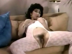The crotchless catsuit : A girl who is dressed in her underwear walks into a room where two guys and another girl are at the table. A little later she is laying down wearing a crotchless catsuit. She lowers the top of it and plays with her giant boobs.