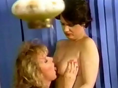 Transsexual neighbour : A blonde woman opens the door to a female neighbour who is bringing her a welcome present. A little later both of them are in the bedroom and the blonde girl is licking the other ones tits. When she takes her dress off the blonde girl appears to be a transsexual.