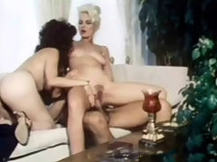 Seka in a threesome : A couple is sitting on a couch watching a blond girl who is stripping right opposite them. A little later both girls are naked and sucking the guys dick in turns. Then the blonde girl sits on the guys lap to get fucked while the other girl is licking her tits.