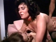 Vintage threesome : Two women visit a guy who welcomes them with a gun in his hand. A little later he is fucking one of them on the bed while the other watches. After a while the second girl joins the couple on the bed and sucks the guys dick until he fucks her as well.