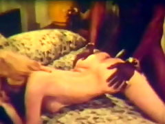 Interracial threesome : A naked blonde girl is laying on the bed with two black guys on her side. They kiss her and massage her hairy pussy. She suck both dicks before she gets on her knees so one of the guys can fuck her from behind.
