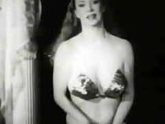 Vintage striptease : A long haired woman in a ballroom dress enters the stage and begins to dance to the music. She bends over to the camera, showing her large tits. SUddenly she takes her dress off and dances on in a small bikini.