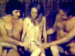 reluctant threesome : A very skinny looking girl with small tits is sitting in between two guys who take her panties off. A little later she is on her knees, sucking one guys cock and getting fucked by the other one at the same time.