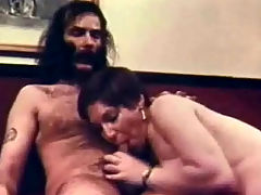 Milf in a rim job : A very hairy looking guy is sitting on a couch where a middle aged woman is giving him a good blow job. A little later he lifts his legs up so she can lick his asshole. Then he fucks here, making her scream with pleasure.