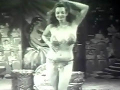Vintage exotic dancer : A woman with large tits and dressed in a bikini and a sweeping veil is dancing on a stage, swaying her boobs about. She drops her veil, revealing her long legs. She continues to dance, showing her body off to the camera.