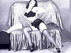 Betty Paige posing : A girl with long black hair wearing a bathrobe is laying down on a couch. She gets up and opens the robe, showing she is only wearing undies, nylons and high heels.