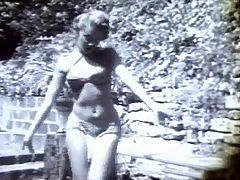 Blonde girl dancing : A young, blonde girl in a gym suit is dancing around in the garden, making seductive movements towards the camera. A little later she is only wearing a bikini, doing a belly dance and swaying her body to and fro.