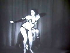 Exotic dancer : The famous stripper Kalantan is dancing on a stage, dressed in a black, exotic bikini and high heels. She sways her hips about, showing her slim body off to the camera.