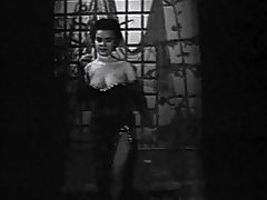 Oldfashioned showgirl : In this black and white movie from the 1950s we see a young woman in an evening dress enter a stage where she begins to dance around. She removes her dress and shows her large tits off. Later on she plays with her naked breasts.