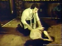Vintage rape scene : A man and a woman are on the floor of the living room. He is forcibly removing her clothes while she protests in a loud voice. When she is naked, the guy fucks her hard, folding her legs against her chest to penetrate her deeper.