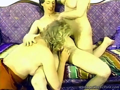 Transsexual threesome : A guy is sitting on a couch. There is a blonde transsexual on her knees next to him sucking his dick while he is licking another girls tits. Then both girls suck his dick in turn before he fucks the transsexual in his asshole.