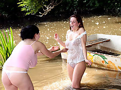 Lesbian fun at the riverside : Two busty teens are playing with each other in the river, splashing each other with water which makes their shirts transparent. One of the girls lowers her shirt so the other one can play with her tits. When they are both naked they fuck one another with a dildo.
