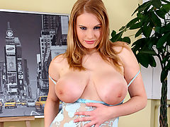 Busty redhead at play : A young girl in a transparent dress is showing her body off to the camera. Lowering her dress she reveals her enormous tits. She plays with them for a while, squeezing and stroking them. Then she plays with her soaking wet pussy.