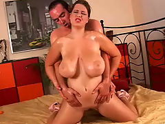 Girl with big boobs gets fucked : A young girl with big tits is sitting on a bed. She does a slow striptease and when she is completely naked a guy approaches her. She suck his long dick, massaging it with her hands. He then fucks her until he comes over her tits.