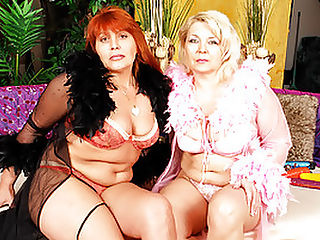Blond Granny Claudie Fucks Karen with Dildo : Claudie and Karen are dressed to the nines in heels, fancy lingerie, and feather boas. After all, these lesbian grannies still got it where it counts! Sexy blond Claudie pops out one of her boobs for Karen to suck on. Obediently, Karen bends over and lets Claudie grace her soft hands up and around her inner thighs, electrifying her with pure bliss! Sliding her thong to the side, Claudie starts small with a glass dildo and wriggles it in Karens wide pussy hole. With her fingers, she reveals Karens clit and tongue-fucks the man in the canoe til Karen orgasms!