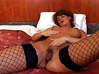 Mature Whore In Fishnets Takes Black Rod : Lovers of fishnets - this hardcore mature interracial clip is for you! Despite the fact that she must pushing 40, this redhead stunner has got an incredible, perfectly shaped hourglass body. Her top half is wrapped up in a tight black corset that shows off her perfect little tits and shapely waist and those fine, long legs are perfectly clad in fishnets that make her calves seem to go on for ever! She swallows the cock of her black stud bareback, squatting like a whore and fingering her own hole while she blows her man. Then she lies back on the bed, her man holding her legs apart by the ankles while he deep strokes her snatch.