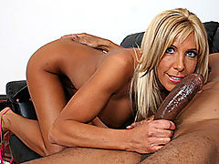 Busty Blonde MILF Strokes A Black Cock : Busty blonde MILF Misty Vonage is introduced and answers some questions while she sits on the coach. Shes a horny cougar, and she takes off her skimpy pink top and bra to free her large fake tits. She drops her skirt and panties to show off her pretty bald pussy and fine ass before shes joined by an eager black dude. She greedily takes hold of his hard cock and gets to work jacking him off. She plays with his balls as she strokes his big dick, and he finally cover her breasts in his hot cum as she milks out every last drop.